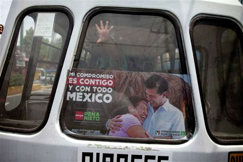La ventana trasera de un minib�s con propaganda electoral a favor del candidato presidencial del Partido Revolucionario Institucional, el ex gobernador del Estado de M�xico Enrique Pe�a Nieto, en esta fotograf�a del viernes 29 de junio de 2012, en la ciudad de M�xico. M�xico vota en comicios presidenciales el domingo 1 de julio de 2012. (Foto AP/Esteban F�lix) Photo: Associated Press