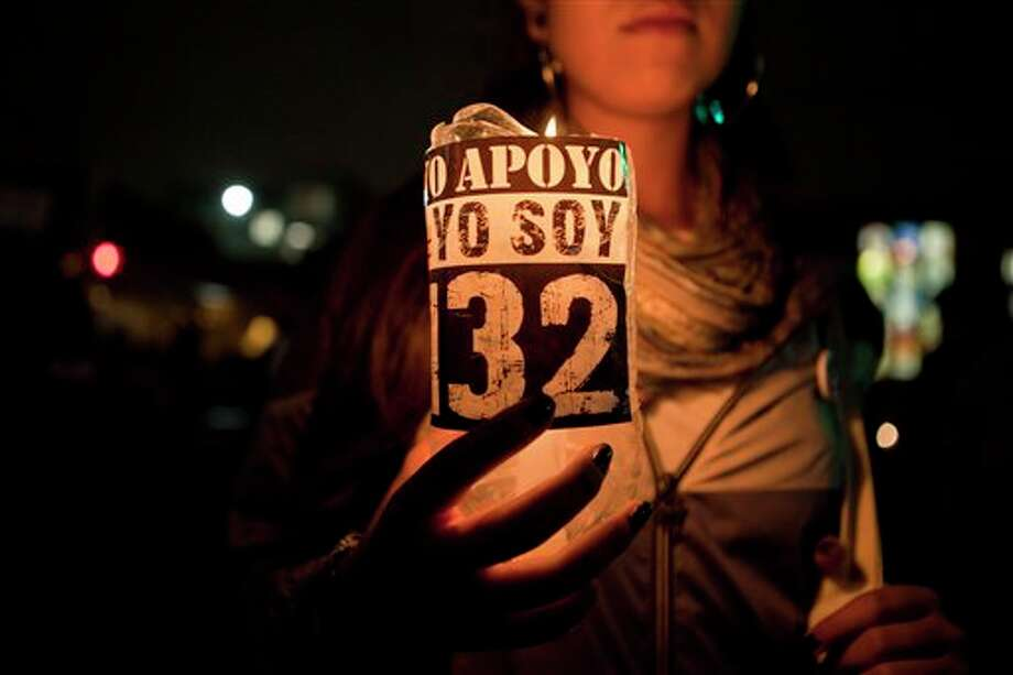 "A supporter of the ""I am 132"" movement holds up a candle during a march in silence with torches and candles in Mexico City, Saturday, June 30, 2012. The movement, which began in opposition of the alleged biased coverage by the media of  the 2012  elections and against the front running candidate Enrique Pena Nieto of the Revolutionary Institutional Party (PRI), are now demanding that the electoral institute does not rig the results in Sunday's July 1 elections. (AP Photo/Christian Palma) Photo: Associated Press"