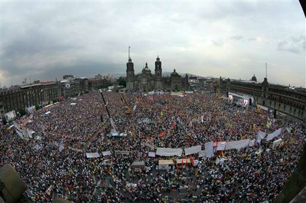 People attend the closing rally of Mexican presidential candidate Andres Manuel Lopez Obrador of the Democratic Revolution Party (PRD) at the main Zocalo plaza in Mexico City, Wednesday, June 27, 2012. Mexico will hold presidential elections on July 1. (AP Photo/Marco Ugarte) Photo: Associated Press