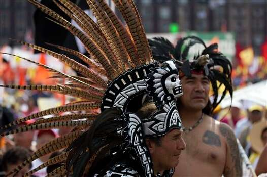 Supporters of Andres Manuel Lopez Obrador, presidential candidate for the Democratic Revolution Party (PRD), dressed in pre-Columbian attire wait for his arrival during the closing rally of his campaign at the main Zocalo plaza in Mexico City, Wednesday, June 27, 2012. General elections in Mexico are scheduled for Sunday, July 1. (AP Photo/Esteban Felix) Photo: Associated Press