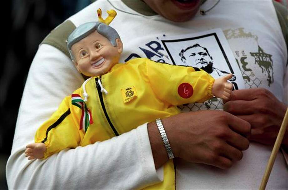 A supporter of Andres Manuel Lopez Obrador, presidential candidate for the Democratic Revolution Party (PRD) carries a toy representing Lopez Obrador as he head towards the main Zocalo plaza to participate in Lopez Obrador's final campaign closing rally in Mexico City, Mexico, Wednesday, June 27, 2012. Next July 1, Mexico will hold presidential elections. (AP Photo/Eduardo Verdugo) Photo: Associated Press