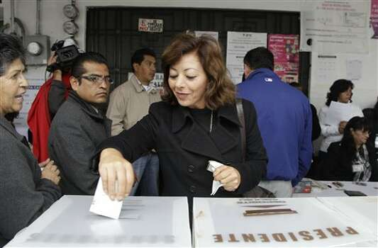 A woman casts her vote during general elections in Atlacomulco, Mexico, Sunday, July 1, 2012. Mexico's more than 79 million voters head to the polls Sunday to elect a president, who serves one six-year term, as well as 500 congressional deputies and 128 senators. (AP Photo/Dario Lopez-Mills) Photo: Associated Press