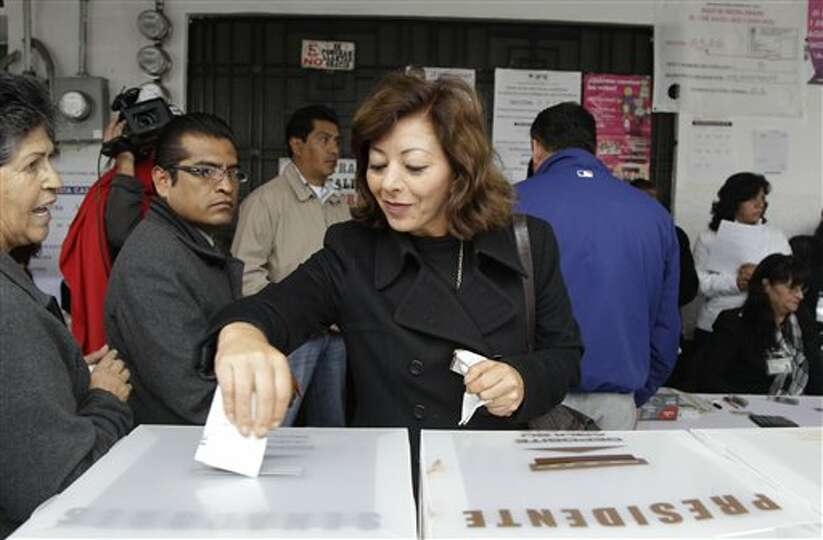 A woman casts her vote during general elections in Atlacomulco, Mexico, Sunday, July 1, 2012. Mexico