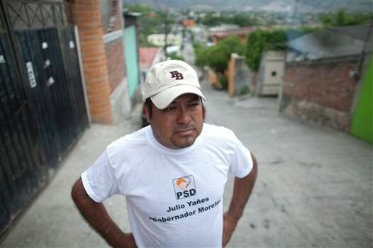 In this photo taken on Thursday, June 21, 2012, mayoral candidate Saul Garcia stands in front of his home, weeks after men on a motorcycle shot his front gate and left a message on the behalf of a drug cartel warning him to withdraw from the race or the gang would kill him and his family, in Emiliano Zapata, Morelos. As Mexicans head to the ballot box Sunday, drug cartels are registering their votes with scare tactics and cold, hard cash to make sure whoever is elected doesn�t interfere with their lucrative operations. (AP Photo/Alexandre Meneghini) Photo: Associated Press