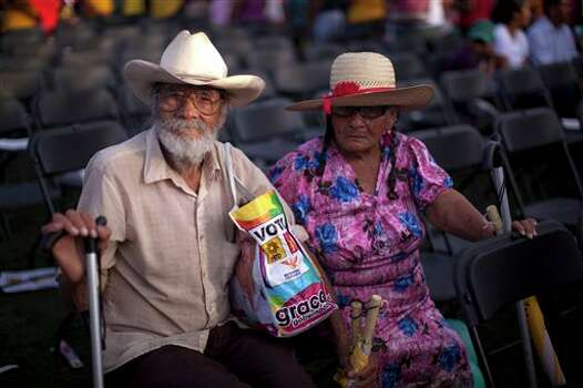 In this photo taken on Thursday, June 21, 2012, a couple prepares to leave a political rally sponsored by gubernatorial candidate Graco Ramirez, in Temixco, on the outskirts of Cuernavaca, Mexico. As Mexicans head to the ballot box Sunday, drug cartels are registering their votes with scare tactics and cold, hard cash to make sure whoever is elected doesn�t interfere with their lucrative operations.  Ramirez says people in remote areas are telling him that gangs are threatening them to stay home on election day. He complains that gunmen approach his campaign staffers while they are out distributing flyers. (AP Photo/Alexandre Meneghini) Photo: Associated Press