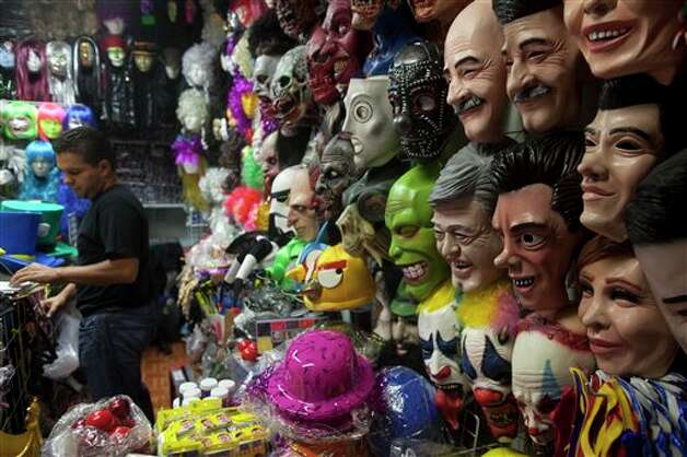 Masks depicting presidential candidates, Josefina Vazquez Mota, for the National Action Party (PAN),  Enrique Pena Nieto, for the opposition Institutional Revolutionary Party, (PRI), Andres Manuel Lopez Obrador, for the Democratic Revolution Party (PRD) and former Mexico's Presidents Carlos Salina de Gortari and Vicente Fox, are displayed for sale among masks depicting some fictional characters in Mexico City, Thursday, June 28, 2012. Mexico will hold its presidential election on July 1. (AP Photo/Esteban Felix)` Photo: Associated Press