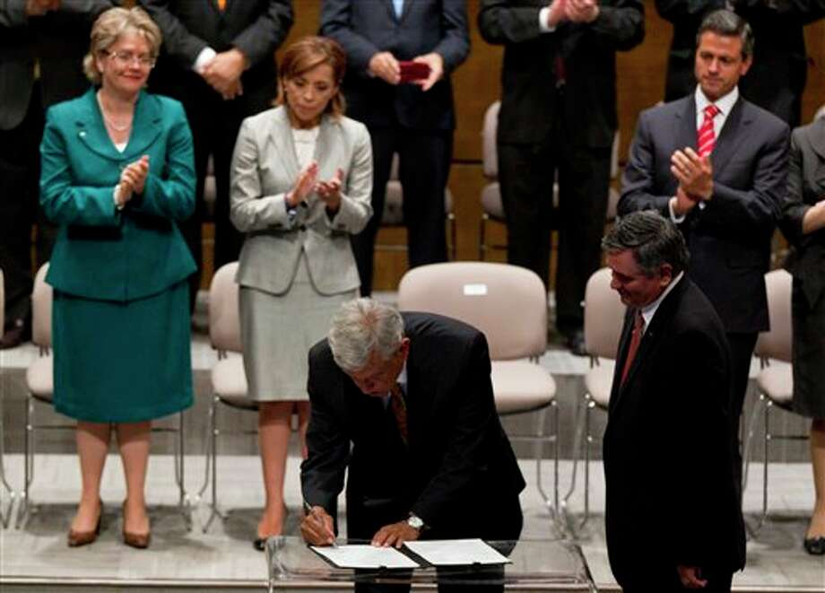 Andres Manuel Lopez Obrador, bottom, left, presidential candidate for the Democratic Revolution Party (PRD) signs an joint agreement with the others candidates to comply with the wishes of the majority, respecting the final results of the July 1 elections in Mexico City, Thursday, June 28, 2012. On top, second from left, Josefina Vazquez Mota, presidential candidate for the National Action Party (PAN), and top right, Enrique Pena Nieto, presidential candidate of the Institutional Revolutionary Party (PRI). (AP Photo/Eduardo Verdugo) Photo: Associated Press