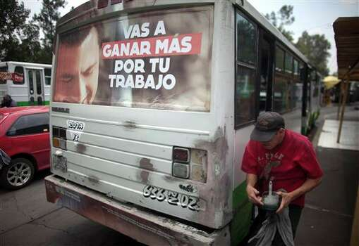 The back of a bus is covered with electoral propaganda supporting presidential candidate Enrique Pena Nieto, of the Institutional Revolutionary Party (PRI), in Mexico City, Friday, June 29, 2012.  Mexico will hold its presidential election on July 1. (AP Photo/Esteban Felix) Photo: Associated Press