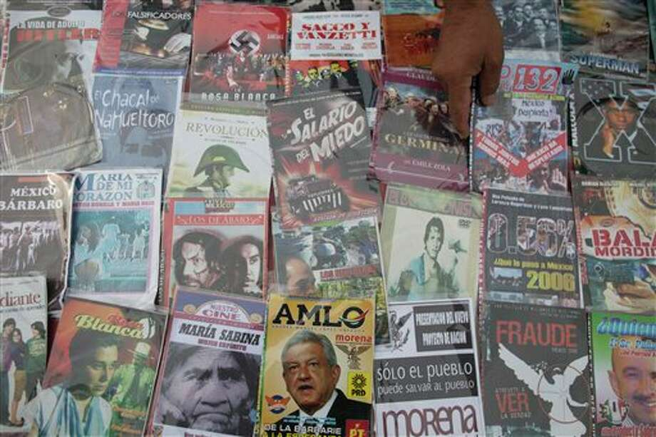 The cover of a DVD shows an image of Andres Manuel Lopez Obrador, presidential candidate for the Democratic Revolution Party (PRD), bottom center, among other movies for sale in the Zocalo plaza in Mexico City, Friday, June 29, 2012. General elections in Mexico are scheduled for Sunday, July 1. (AP Photo/Esteban Felix) Photo: Associated Press