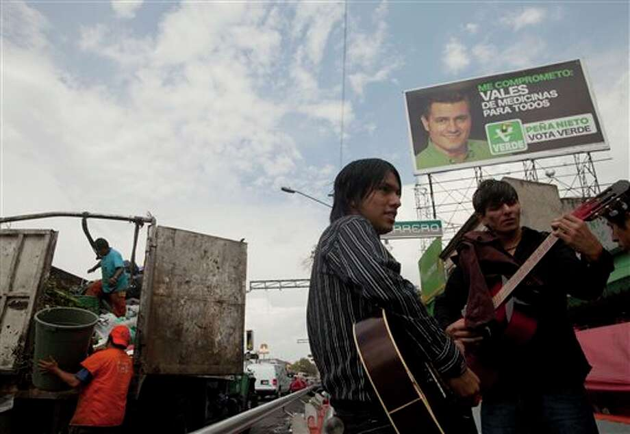 A campaign billboard supporting Enrique Pena Nieto, presidential candidate of the Institutional Revolutionary Party (PRI), stands high as trash collectors work and musicians stand together in Mexico City, Friday, June 29, 2012. Mexico will hold presidential elections on July 1. (AP Photo/Esteban Felix) Photo: Associated Press