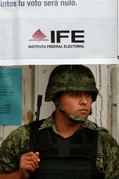 A soldier stands guard outside a voting center run by the Federal Electoral Institute (IFE) ahead of elections in Mexico City, Saturday, June 30, 2012. Mexico will hold general elections, including the presidential election, on July 1. (AP Photo/Marco Ugarte) Photo: Associated Press