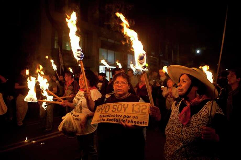 "Supporters of the ""I am 132"" movement  march in silence with torches  in Mexico City, Saturday, June 30, 2012. The movement, which began in opposition of the alleged biased coverage by the media of  the 2012  elections and against the front running candidate Enrique Pena Nieto of the Revolutionary Institutional Party (PRI), are now demanding that the electoral institute does not rig the results in Sunday's July 1 elections. (AP Photo/Christian Palma) Photo: Associated Press"