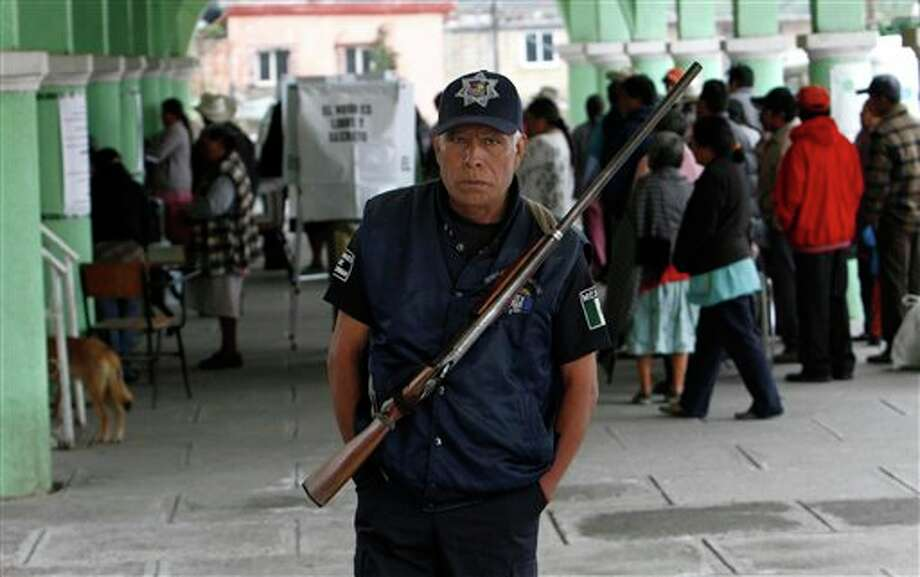 A police officer stands guard outside a polling station, as voters stand in line to vote in the general election, in Santiago Xalitzintla, in the Mexican state of Puebla, Sunday, July 1, 2012. Mexico's more than 79 million voters head to the polls Sunday to elect a president, who serves one six-year term, as well as 500 congressional deputies and 128 senators. (AP Photo/Marco Ugarte) Photo: Associated Press