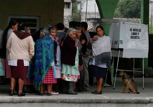 Residents wait in line for their turn to vote in the general election at a polling station in Santiago Xalitzintla, in the Mexican state of Puebla, Sunday, July 1, 2012. Mexico's more than 79 million voters head to the polls Sunday to elect a president, who serves one six-year term, as well as 500 congressional deputies and 128 senators. (AP Photo/Marco Ugarte) Photo: Associated Press