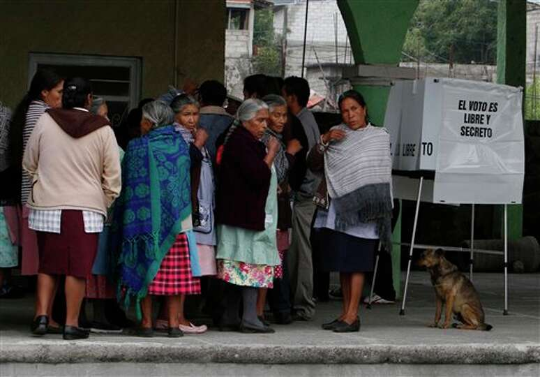 Residents wait in line for their turn to vote in the general election at a polling station in Santia