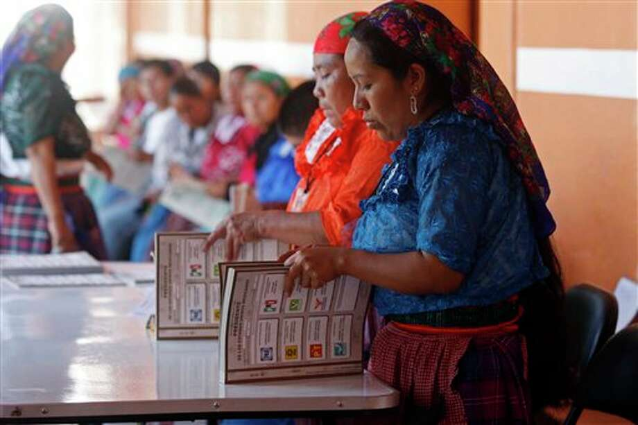 Electoral workers prepare ballots at a polling station in Oaxaca, Mexico, Sunday, July 1, 2012. Mexico's more than 79 million voters head to the polls Sunday to elect a president, who serves one six-year term, as well as 500 congressional deputies and 128 senators. (AP Photo/ Luis Alberto Cruz) Photo: Associated Press