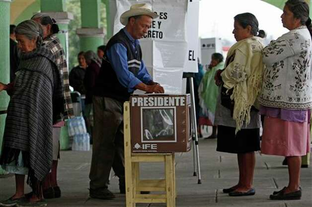 A men casts his ballot for president at a polling station in Santiago Xalitzintla, in the Mexican state of Puebla, Sunday, July 1, 2012. Mexico's more than 79 million voters head to the polls Sunday to elect a president, who serves one six-year term, as well as 500 congressional deputies and 128 senators. (AP Photo/Marco Ugarte) Photo: Associated Press