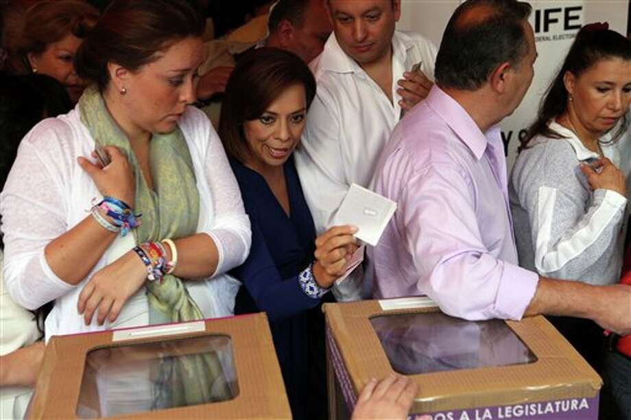 Josefina Vazquez Mota, second from left, presidential candidate of the ruling National Action Party (PAN), makes her way between voters to cast her vote for Congress representatives during the general elections in Huixquilucan, Mexico, Sunday, July 1, 2012. (AP Photo/Andres Leighton) Photo: Associated Press