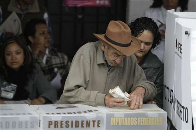 A men casts one his ballots at a polling station in  Atlacomulco, Mexico, Sunday, July 1, 2012. Mexico's more than 79 million voters head to the polls Sunday to elect a president, who serves one six-year term, as well as 500 congressional deputies and 128 senators. (AP Photo/Dario Lopez-Mills) Photo: Associated Press