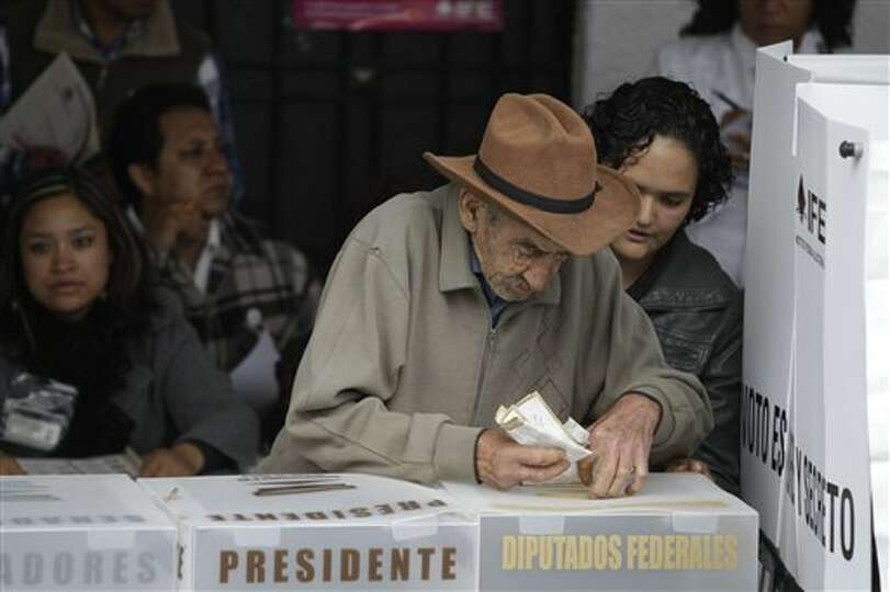 A men casts one his ballots at a polling station in  Atlacomulco, Mexico, Sunday, July 1, 2012. Mexi