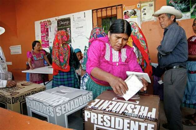 A woman casts her ballot at a polling station in Oaxaca, Mexico, Sunday, July 1, 2012. Mexico's more than 79 million voters head to the polls Sunday to elect a president, who serves one six-year term, as well as 500 congressional deputies and 128 senators. (AP Photo/ Luis Alberto Cruz) Photo: Associated Press