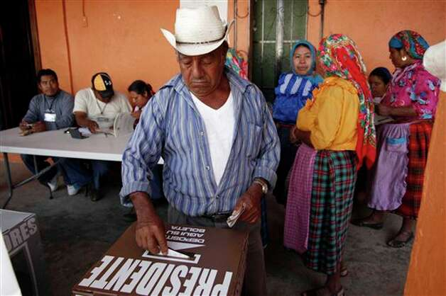 A man casts his ballot for president at a polling station in Oaxaca, Mexico, Sunday, July 1, 2012. Mexico's more than 79 million voters head to the polls Sunday to elect a president, who serves one six-year term, as well as 500 congressional deputies and 128 senators.  (AP Photo/ Luis Alberto Cruz) Photo: Associated Press