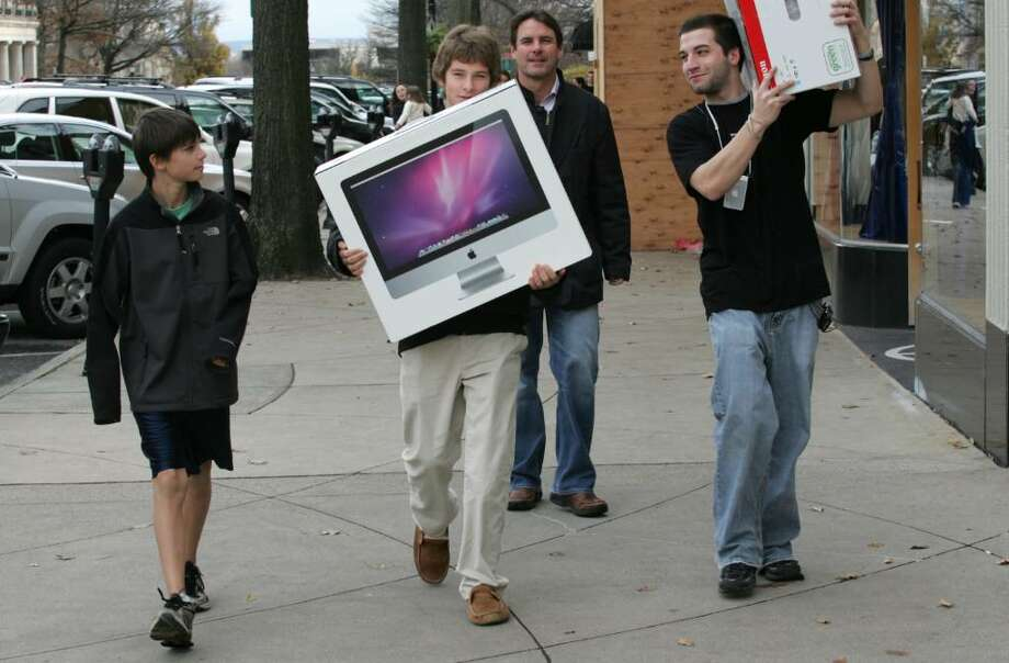 Mitchell, Dylan, and Sean O'Connor, along with Apple employee Mike Oria, carry a Christmas gift back to the car on Greenwich Avenue during Black Friday. Photo: David Ames / Greenwich Time