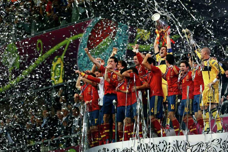 Spanish players celebrate with the trophy after defeating Italy 4-0 in the Euro 2012 soccer champion