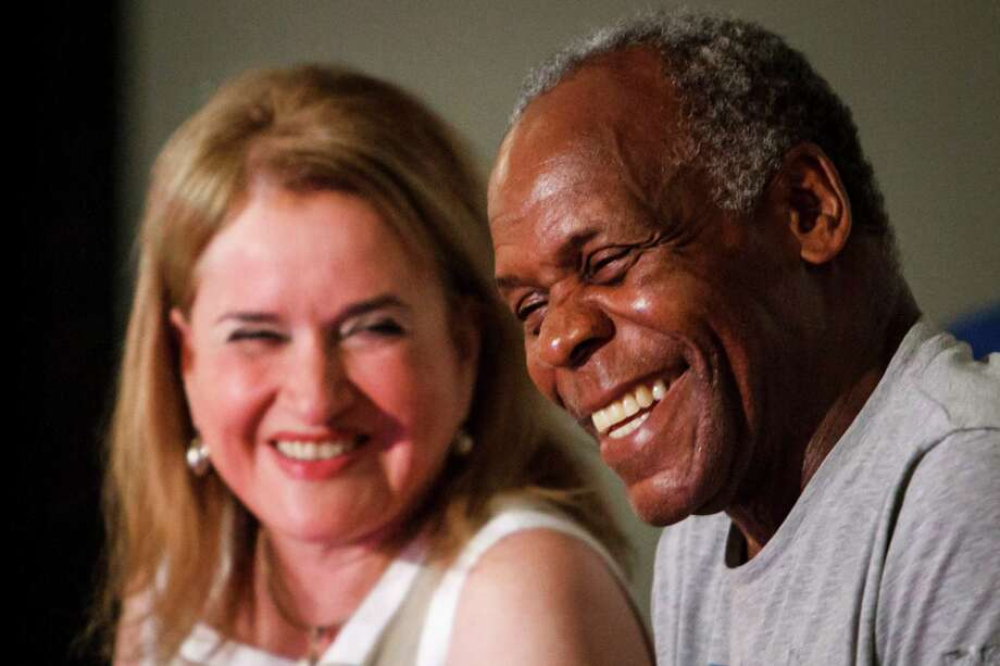 Danny Glover, right, laughs with Sylvia Garcia during a Town Hall Meeting at the Third Ward Multi-Services Center, Sunday, July 1, 2012, in Houston.  Civil rights activist and famed actor Danny Glover visited Houston to meet with a delegation of janitors who clean some of the city's most exclusive real estate - including buildings owned by JP Morgan Chase, Exxon and Shell - but make just $9,000 annually. Photo: Michael Paulsen, Houston Chronicle / © 2012 Houston Chronicle