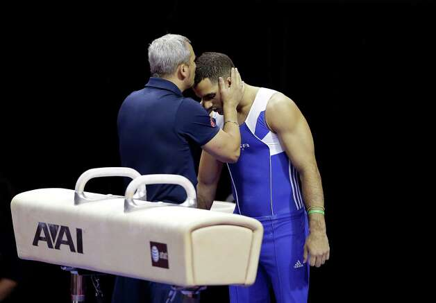Coach Yin Alvarez, left,  give his son Danell Leyva encouragement before he competes on the pommel horse during the preliminary round of the men's Olympic gymnastics trials Thursday, June 28, 2012, in San Jose, Calif.  (AP Photo/Gregory Bull) Photo: Associated Press