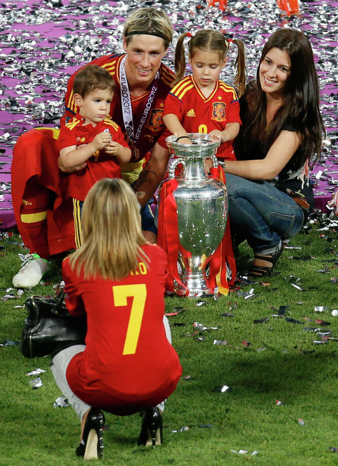 Spain's Fernando Torres, his wife Olalla, right, pose with the trophy for a photograph after Spain won the Euro 2012 soccer championship final  between Spain and Italy in Kiev, Ukraine, Monday, July 2, 2012. Photo: AP