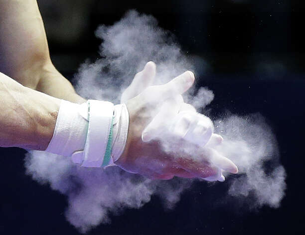 Chris Brooks prepares his hands before competing on the rings during the preliminary round of the men's Olympic gymnastics trials Thursday, June 28, 2012, in San Jose, Calif.  (AP Photo/Gregory Bull) Photo: Associated Press