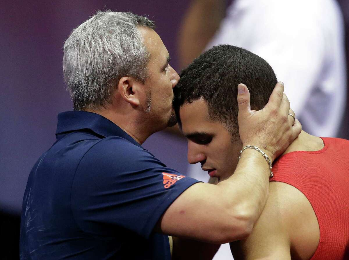 Coach Yin Alvarez, left, kisses his son, Danell Leyva, before he performs on the parallel bars during the final round of the men's Olympic gymnastics trials, Saturday, June 30, 2012, in San Jose, Calif. Leyva won the men's all-around competition and will be on the U.S. Olympic team. (AP Photo/Jae C. Hong)
