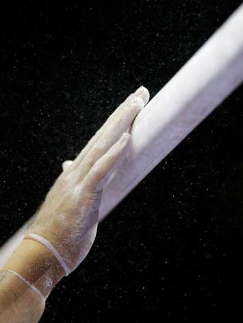 A competitor prepares the parallel bars for competition before the start of the final round of the men's Olympic gymnastics trials, Saturday, June 30, 2012, in San Jose, Calif. (AP Photo/Gregory Bull) Photo: Associated Press