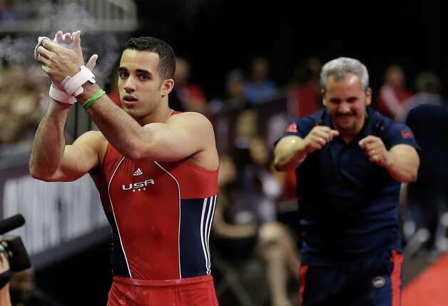 Danell Leyva, left, and his step father, Yin Alvarez, react after Leyva's performance on the horizontal bar during the final round of the men's Olympic gymnastics trials, Saturday, June 30, 2012, in San Jose, Calif. (AP Photo/Gregory Bull) Photo: Associated Press