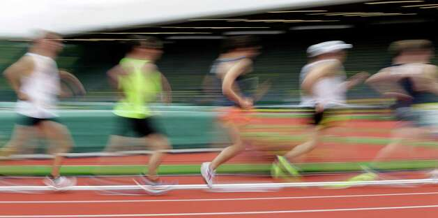 In this image made with a slow shutter speed, athletes compete in the men's 20 kilometer race walk at the U.S. Olympic Track and Field Trials athletics meet, Saturday, June 30, 2012, in Eugene, Ore. (AP Photo/Eric Gay) Photo: Associated Press