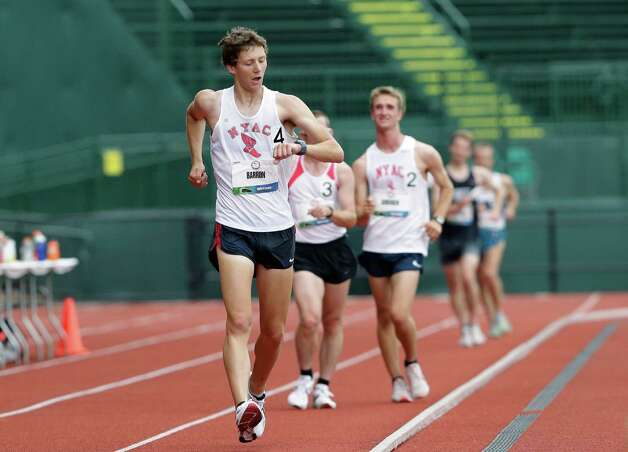 Trevor Barron, front, checks his watch as he competes in the men's 20 kilometer race walk at the U.S. Olympic Track and Field Trials athletics meet, Saturday, June 30, 2012, in Eugene, Ore. Barron won with a time of 1:23:00.10. (AP Photo/Eric Gay) Photo: Associated Press