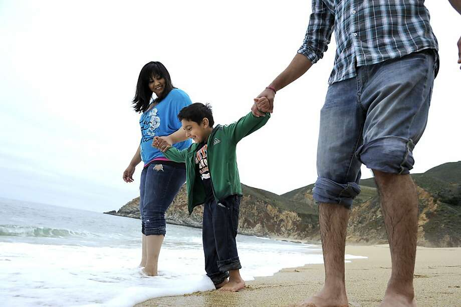 Pittsburg's Pawan Singh, right, wife Navi and son Jasmit visit Gray Whale Cove State Beach in Montara Friday. Photo: Michael Short, Special To The Chronicle
