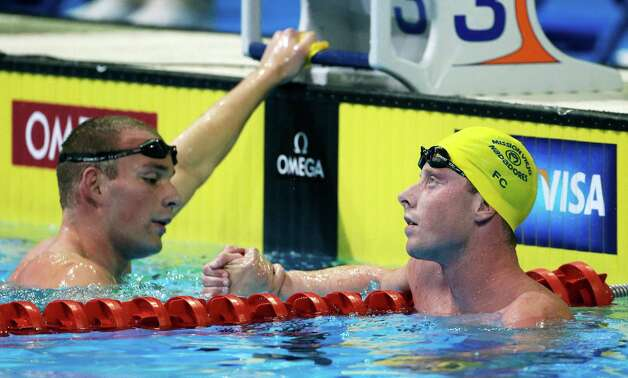 Ryan Feeley, left, and Chad LaTourette shake hands after swimming in the men's 1500-meter freestyle preliminaries at the U.S. Olympic swimming trials on Sunday, July 1, 2012, in Omaha, Neb. (AP Photo/Mark Humphrey) Photo: Associated Press