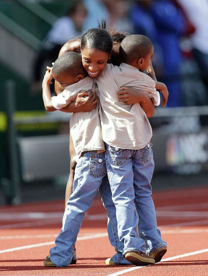 Lashinda Demus hugs her sons Dontay, right, and Duaine after finishing first in the women's 400 meter hurdles at the U.S. Olympic Track and Field Trials Sunday, July 1, 2012, in Eugene, Ore. Photo: Marcio Jose Sanchez