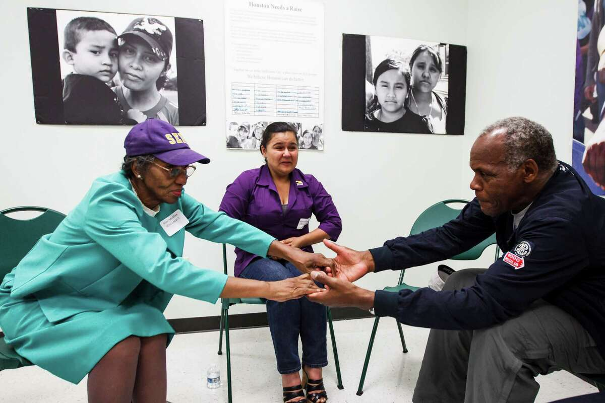 Alice McAfee, left, shakes hands with Danny Glover after sharing her hardships providing for her family on janitor wages as Adrianna Vasquez, center, looks on during a Town Hall Meeting with Danny Glover at the Third Ward Multi-Services Center, Sunday, July 1, 2012, in Houston. Civil rights activist and famed actor Danny Glover visited Houston to meet with a delegation of janitors who clean some of the city's most exclusive real estate - including buildings owned by JP Morgan Chase, Exxon and Shell - but make just $9,000 annually. ( Michael Paulsen / Houston Chronicle )