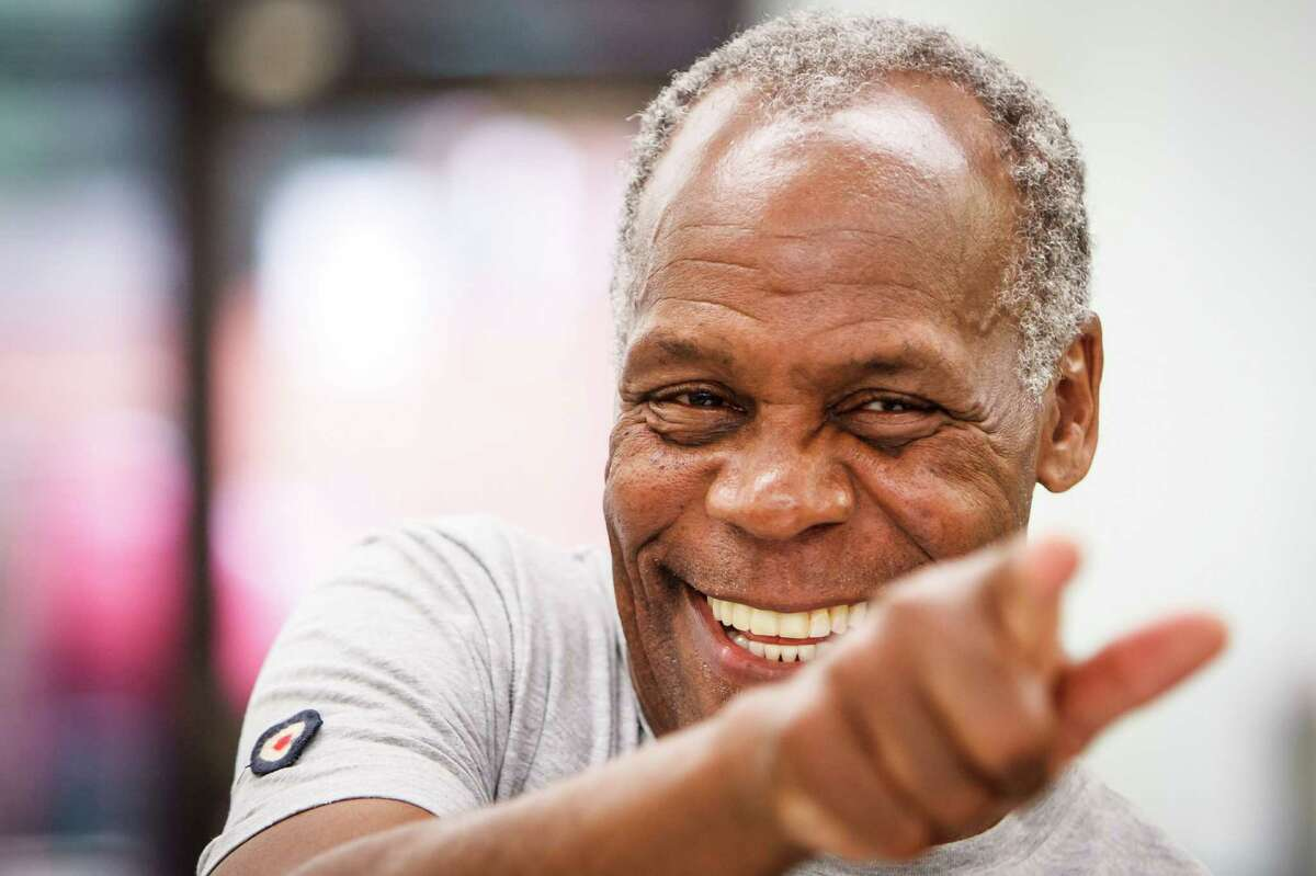 Danny Glover points towards a friend during a Town Hall Meeting at the Third Ward Multi-Services Center, Sunday, July 1, 2012, in Houston. Civil rights activist and famed actor Danny Glover visited Houston to meet with a delegation of janitors who clean some of the city's most exclusive real estate - including buildings owned by JP Morgan Chase, Exxon and Shell - but make just $9,000 annually. ( Michael Paulsen / Houston Chronicle )