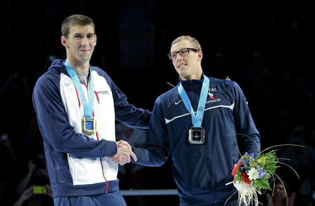 Michael Phelps, left, and Tyler McGill shake hands during the medal ceremony for the men's 100-meter butterfly at the U.S. Olympic swimming trials on Sunday, July 1, 2012, in Omaha, Neb. (AP Photo/Mark Humphrey) Photo: Associated Press