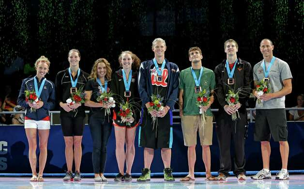 Jimmy Feigen (second from right) stands with other members of the Olympic swim team after receiving his medal as an Olympian and member of the 4x100 freestyle relay lineup. He finished fifth in the men's 50-meter freestyle finals Sunday, with the top two qualifying in the event for the Olympics. Also posing during the medal ceremony are Alyssa Anderson (from left), Amanda Weir, Natalie Coughlin, Shannon Vreeland, Matt McLean, Charlie Houchin and Jason Lezak. (AP Photo/Mark Humphrey) Photo: Associated Press
