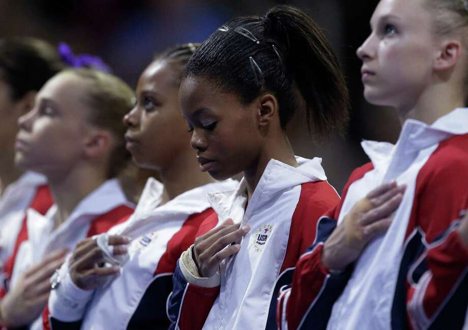Gabby Douglas stands with other competitors during the playing of the national anthem during the final round of the women's Olympic gymnastics trials, Sunday, July 1, 2012, in San Jose, Calif. Photo: Jae C. Hong