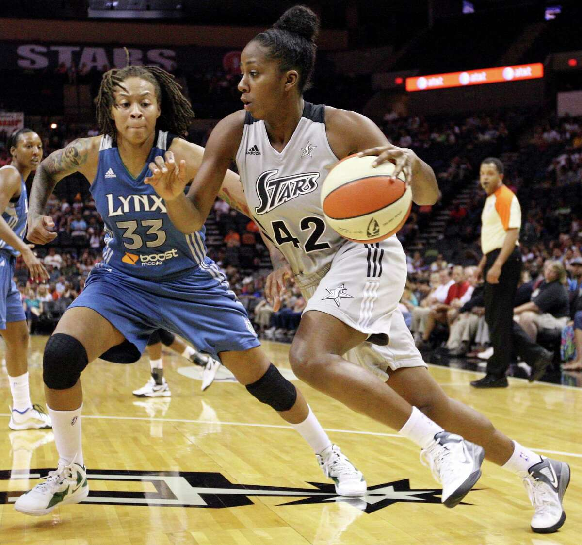 The Silver Stars' Shenise Johnson looks for room around the Minnesota Lynx's Seimone Augustus during first half action on Sunday, July 1, 2012, at the AT&T Center.