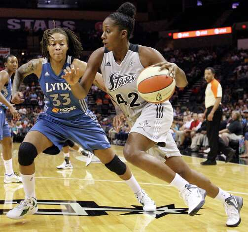 The Silver Stars' Shenise Johnson looks for room around the Minnesota Lynx's Seimone Augustus during first half action on Sunday, July 1, 2012, at the AT&T Center. Photo: Edward A. Ornelas, San Antonio Express-News / © 2012 San Antonio Express-News