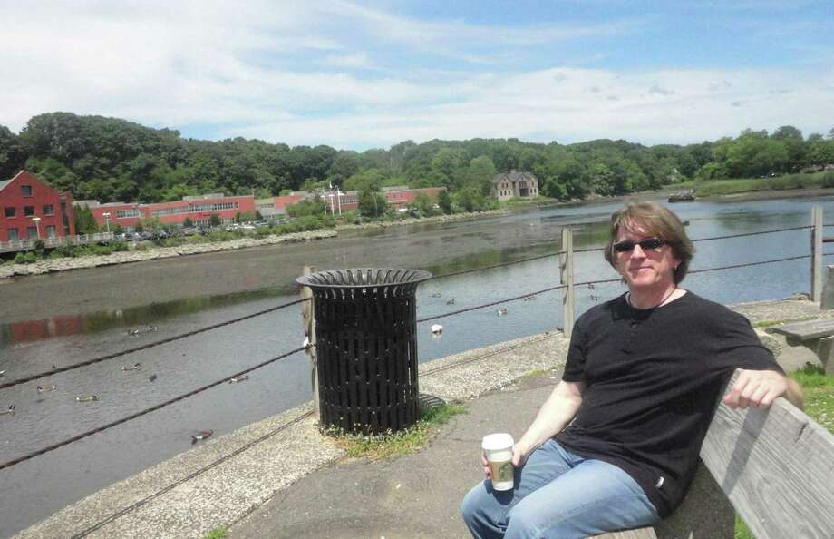 Mark Derosa relaxes on a bench next to the Saugatuck River in downtown Westport this week. Photo: Nicoletta Richardson / Westport News contributed