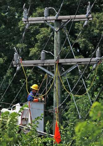 A member of Pike Electric works on utility pole Saturday, June 30, 2012 in Springfield Va. A severe storm late Friday, June 29th knocked out power to approximately one million residents, traffic signals and businesses in the  region. (AP Photo/Pablo Martinez Monsivais) Photo: Pablo Martinez Monsivais