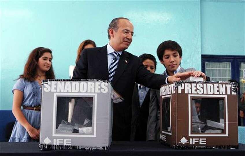 El mandatario saliente de M�xico, Felipe Calder�n, acompa�ado de sus hijos, deposita su voto e